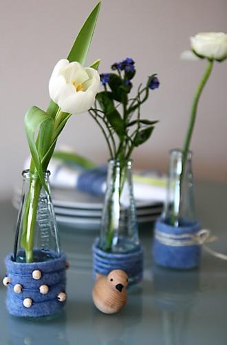 Gläschen auf Tisch mit Blumen arrangiert