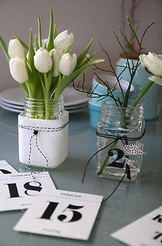 Tulpen im Glas mit Filz ummantelt und Kalenderblätter auf Tisch